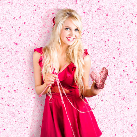 gorgeous girl: Sweet blond lady holding ball of heart shaped wool with knitting needles . Knitting love
