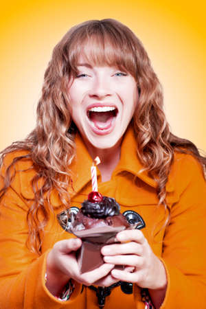 gusto: Happy excited  birthday girl with her cake and candle cradled in her hands making merry at her party in a warm winter coat on an orange studio background