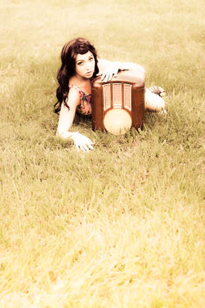 bygone: Landscape Portrait Of A Woman Laying In Grass Field With A Old Fashioned Antique Retro Radio In A Bygone And Reminiscent Image From A Past Era