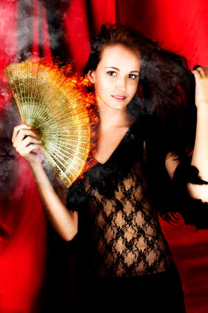 broadway show: In A Show Of Smoke And Flames A Hot Woman Theatre Performer Dances On A Broadway Stage With A Flame Fan, In A Image Titled Hot Female Fire Dancer Stock Photo