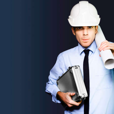 driven: Driven and determined young male engineer in building hardhat carrying briefcase and blueprint on dark blue copyspace background