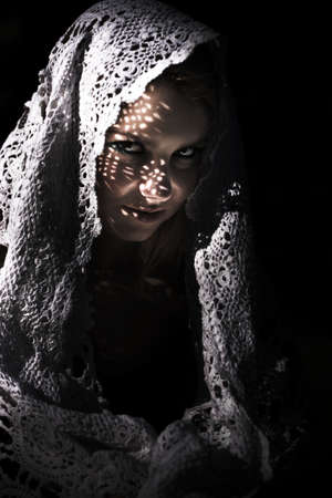 draped: Mysterious Sinister Woman In Shawl. A young mysterious woman peers out from under a lacy shawl in the sinister darkness.