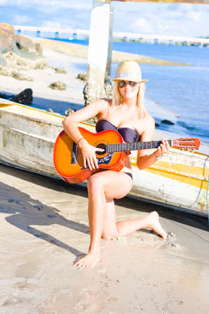 paradise bay: Happy Entertaining Performer Girl With Smile Kneeling Down On One Knee Holding Guitar In Tropical Island Paradise, Boat Bay And Sky Background Stock Photo