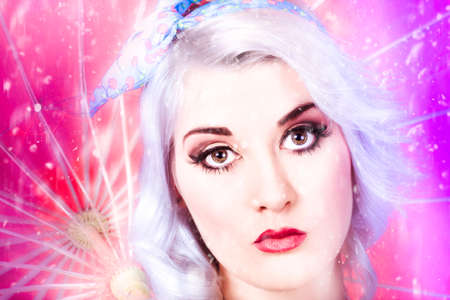 rinse: Closeup face portrait of a pinup model in colourful make-up walking through a dream of falling rain droplets with bleached white short hair and purple rinse Stock Photo