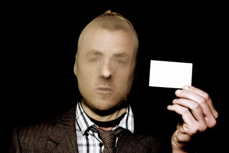 Artful dodgy salesman with business card and a stocking mask going about his nefarious business of deception and fraud