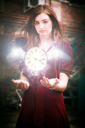 time flies: Time Flies With Magic And Grace From The Hands Of A Woman In A Red Dress With The Suspended Clock With Wings Glows In A Enchanting Take Off