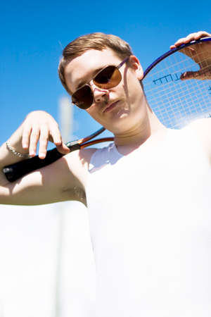 70s tennis: A Vintage Player Rests Up On His Racquet Between Serves During A Tennis Tournament In A Retro Flashback To 1970 Stock Photo