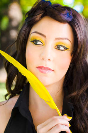preoccupied: Touching Animal And Nature Image Of A Woman Holding A Soft Bright Yellow Bird Feather With Matching Makeup Outside In A Tender Caring And Gentle Portrait