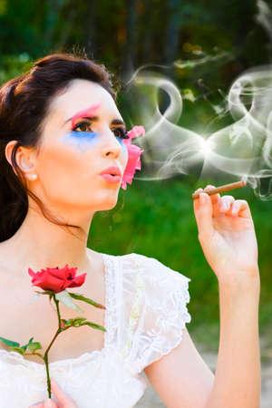 person smoking: Un pensamiento rom�ntico surge en la mente de un amor Golpeado mujer a medida que sopla un coraz�n simb�lico en forma de nube de humo a la atm�sfera de romance