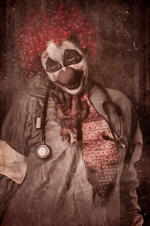 autopsy: Funny portrait of an evil vintage clown doctor getting chocked by a chopped off hand inside autopsy clinic. Revenge attack Stock Photo