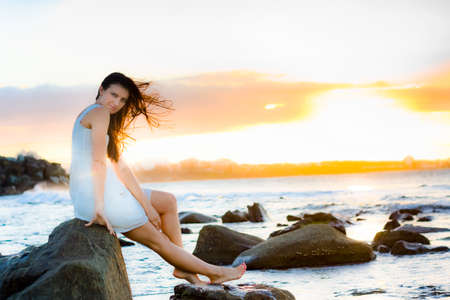 sun down: Wind Blowing In The Hair Of A Beautiful Woman Sitting On A Ocean Rock With A Sun Down Background In A Picturesque And Peaceful Landscape Sunset Beach Portrait