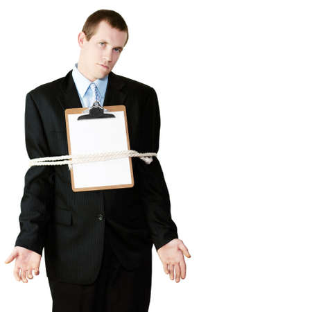 restrictive: Handsome businessman standing with a clipboard with blank paper on his chest and his arms securely tied to his sides by a rope conceptual of being bound by the restrictive regulations of bureaucracy