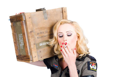 bombshell: Female pinup army solider smoking while holding a crate of explosive small arms in a depiction of courage Stock Photo