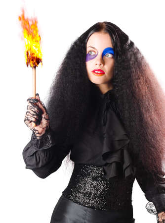 blazes: Woman in black medieval costume with face paint and burning fire torch, white background