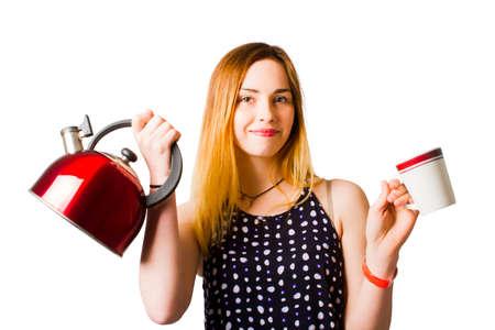 ustensiles de cuisine: Bonne jeune femme tenant une bouilloire et tasse de café quand offrant une autre tasse de thé sur fond blanc Banque d'images