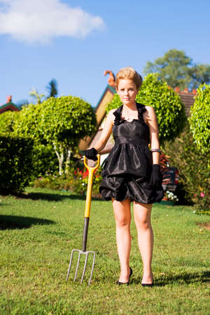 donna ricca: Attractive Rich Woman Tries Her Hand At Being A Do It Yourself Gardener While Standing In Her Front Yard Carrying A Gardening Pitch Fork Archivio Fotografico