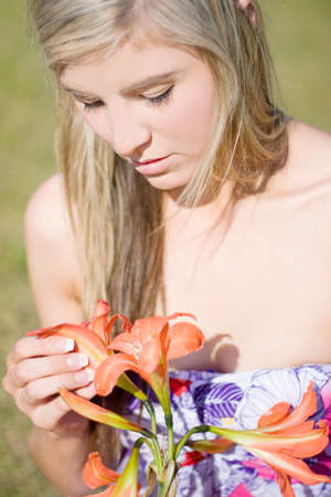 womanliness: A Girl Sitting In A Grassy Meadow Pulls Petals Off A Flower Whilst Chanting He Loves Me He Loves Me Not