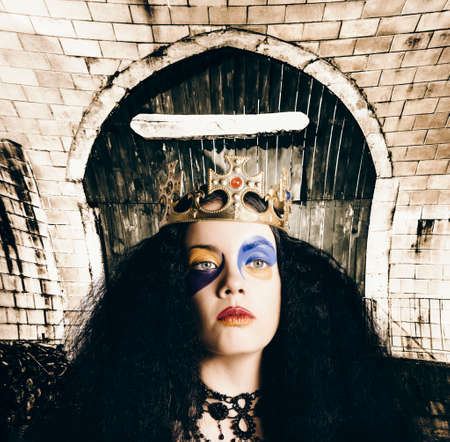 malice: Fashionable grunge queen wearing ruby encrusted crown, wearing bright stylish jester makeup on warped castle background. Malice in wonderland Stock Photo