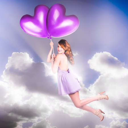 romance sky: Beautiful Vintage Girl With Retro Hair Style Wearing Purple Pin-Up Fashion Flying High In The Sky On The Whim Of A Love Heart Balloon Romance