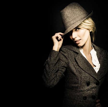 discreto: Oscuro retrato de la manera dramática de una mujer joven y discreta en el elegante sombrero vestían ropa de época, como se ve de nuevo fuera de las sombras de la oscuridad Foto de archivo