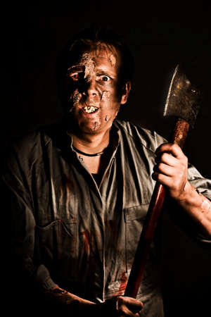 seeks: Decaying reanimated zombie corpse with staring eyes emerges from the shadows wielding a large sharp axe as he seeks a victim to kill Stock Photo
