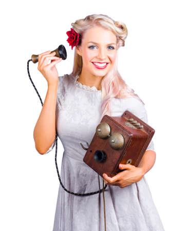 antique telephone: Smiling happy blond woman holding very old antique telephone on white background