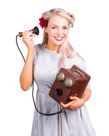 telefono antico: Sorride felice donna bionda che tiene molto vecchio telefono antico su sfondo bianco Archivio Fotografico