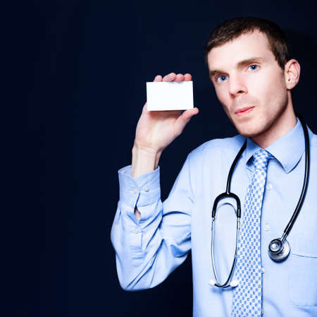 general practitioner: Confident Male General Practitioner Doctor Holding Out Blank Business Card For Medical Clinic Copyspace, On Blue Studio Background Stock Photo
