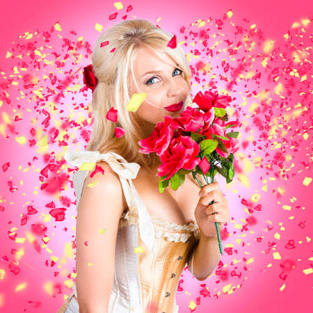 tryst: Creative portrait of a delightful young girl romancing when smelling the scent red flowers amidst falling petals. Falling in love concept Stock Photo