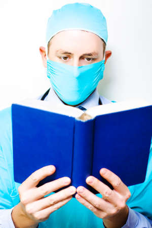 reference book: A masked male doctor stands concentrating on the reference book that he is reading and assimilating in a medical research and study concept Stock Photo