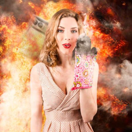 incendio casa: Imagen divertida de una mujer sorprendida cocinar arda el de la cocina en una explosión de fuego y humo. mala cocción Foto de archivo