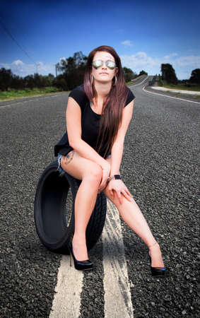 holidaying: In A Travel Industry Concept A Holiday Traveling Tourist On Vacation Sits In The Road On A Car Tyre About To Explore The World On A Travel Trip