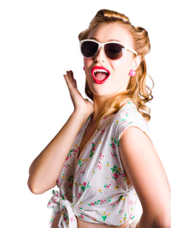 recommendation: Glamorous female pinup with sunglasses wearing pretty dress with floral decoration  shouting out a warning or recommendation on white background Stock Photo