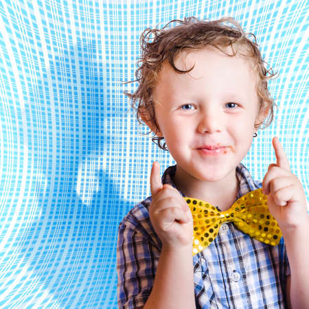 afl: Cute smiling child with chocolate covered face pointing up in approval for Easter time. On blue abstract background