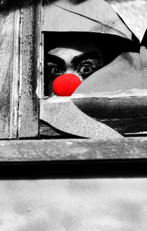 nosey: Peeking Through A Broken Window Pane A Creepy Ghoulish Clown Watches The Halloween Peek A Boo