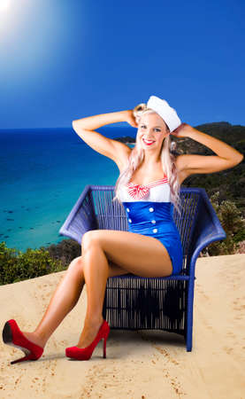 sailor girl: Sexy stylish retro blonde pin-up sailor girl sitting on a beach chair in australia when depicting a beach travel tour Stock Photo