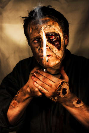 disembodied: Dead Man Smoking. Conceptual image of a living dead man, or zombie, with decaying flesh smoking a cigarette