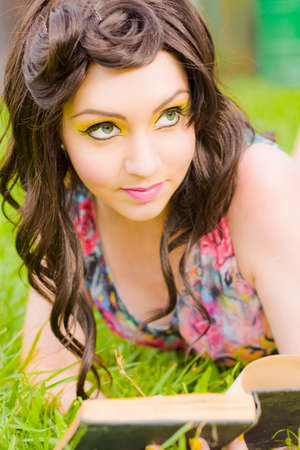 eye liner: Stunning Summertime Woman In Creative Yellow Eye Liner Makeup Reads A Book Of Romantic Tales In A Summer Reading Leisure Escape Stock Photo