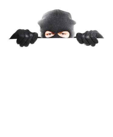ladron: Ladrón que oculta detrás de un cartel en blanco vacío con espacio para el texto, aislado sobre fondo blanco