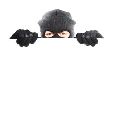 hidden danger: Robber hiding behind a empty white sign with space for text, isolated on white background