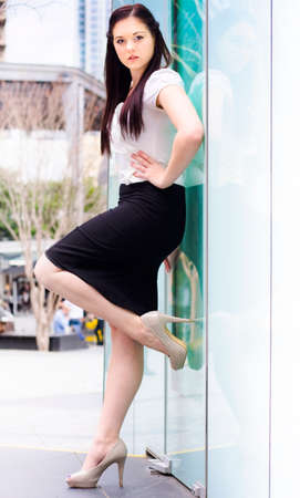 shoes woman: Portrait Of A Confident Young Career Smart Business Woman Opening An Office Glass Door With High Heel Shoe In A Door Of Opportunity And Development Concept Stock Photo