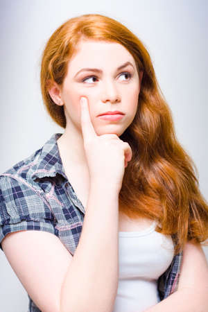 red head: Half Body Photograph Of A Gorgeous Young Red Head Female Holding Pointer Finger To Cheek While Musing Contemplating And Thinking Up Ingenuity And Advancement