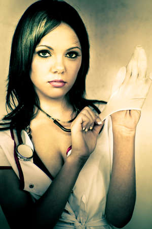 medical checkup: A Healthcare Nurse Provocatively Puts On Rubber Gloves During A Not So Routine Medical Checkup In A Naughty Nurse Conceptual Stock Photo