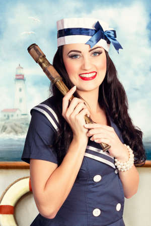 docking: Vintage picture of a smiling young pinup sailor girl in marine uniform holding nautical telescope on maritime ship docking out of port. Sea search and rescue Stock Photo