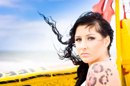 breeze: Head Portrait Of A Surf Girl Enjoying The Ocean Breeze Outdoors Next To A Lifesaver Surfboard