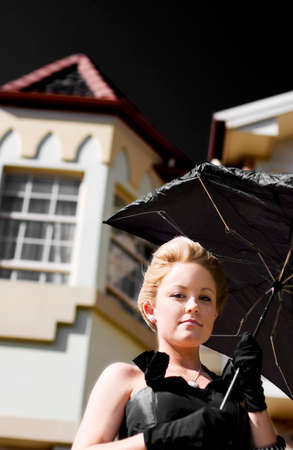 gusty: Woman Standing At The Front Of Her Home Holding A Broken Umbrella From Gusty Winds In Representation Of Weathering The Storm At Home