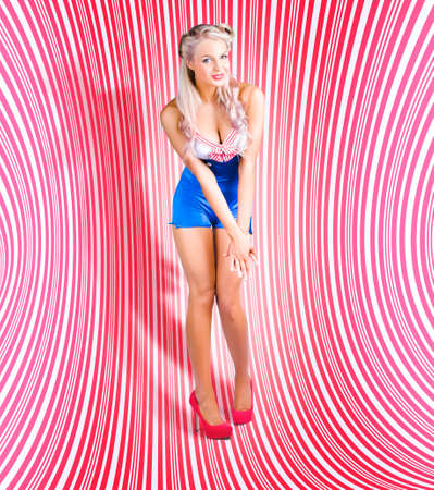 tantalising: Beautiful Blonde Pinup Girl In Stylish Shoes And Cute Sailor Outfit Standing On A Dynamic Red White And Pink Striped Psychedelic Background In A Depiction Of Classic Retro Pin-Up Stock Photo