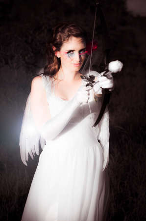 alight: Cupid The Beautiful Goddess Of Love Standing In All White Attire With Wing While Holding A Bow And Rose Arrow Ready To Set Alight The Passion Of Love