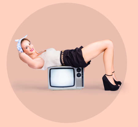 fifties: Old-fashioned retro fitness girl doing sit-up abdominal exercises on television set. Pinup strength concept