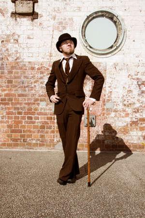 persona caminando: Caballero retro Joven En Traje, sombrero hongo y caminar Antecedentes palillo Wth pared de ladrillo Foto de archivo